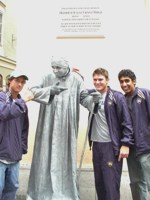 Santiago Montoya, Stephen Bass, and Sheeva Parbhu posing with a man posing as a statue in the streets of Salzburg.