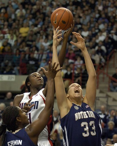 Connecticut's Tina Charles, center, and Melissa D'Amico, right, go for a rebound in the first half.  At left is Crystal Erwin. (AP Photo/Jessica Hill)