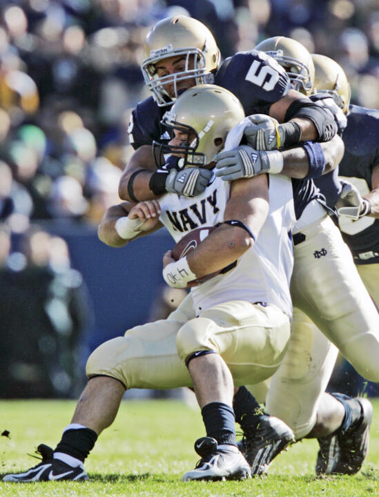 Navy running back Eric Kettani is stopped by  Joe Brockington in the first quarter. (AP Photo/Michael Conroy)