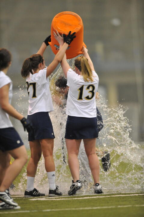Jane Stoeckert (27) and Julie Foote (13) douse head coach Tracy Coyne with a Gatorade shower following Notre Dame's 16-4 win over Duquesne.  The victory was the 100th in the program's history and Coyne's 100th as head coach of the Irish.