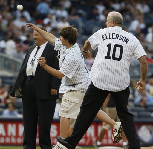 Charlie Weis watches his son Charlie Jr. throw out a ceremonial pitch before the New York-Baltimore game at Yankee Stadium on Monday. (AP Photo/Kathy Willens)