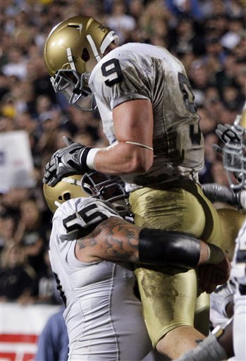 Notre Dame tight end Kyle Rudolph (9) reacts with Notre Dame center Eric Olsen after Rudolph scored on a two-yard touchdown reception during the fourth quarter of an NCAA football game against Purdue in West Lafayette, Ind., Saturday, Sept. 26, 2009. Notre Dame won 24-21.