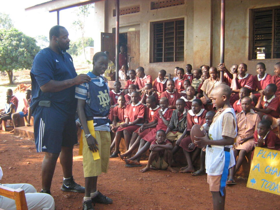 McBride instructs children at St. Jude's Primary School in Jinja about the rules of American football.
