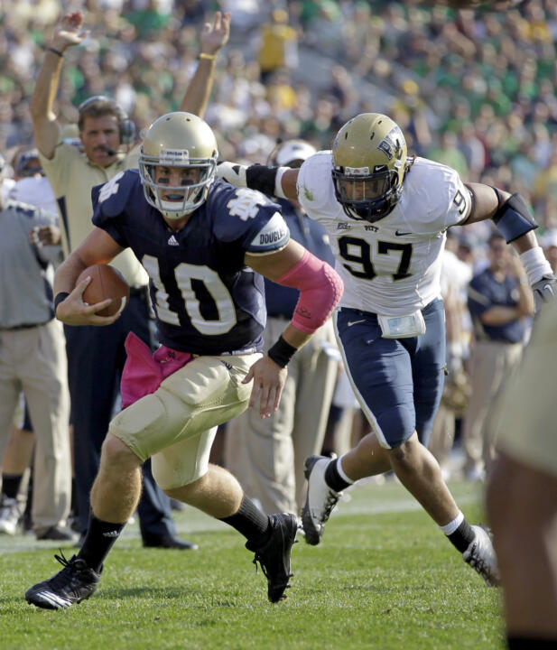 Notre Dame quarterback Dayne Crist eludes Pittsburgh defensive tackle Jabaal Sheard on his way to a 10-yard touchdown.