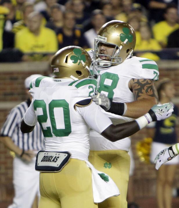 Notre Dame running back Cierre Wood is congratulated by teammate guard Trevor Robinson.