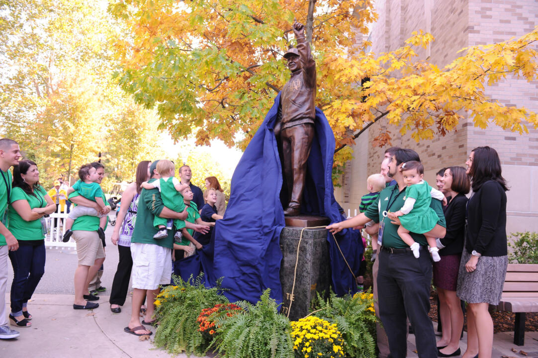Members of the Devine family help unveil the new sculpture outside Gate A of Notre Dame Stadium (photo by Mike Bennett).