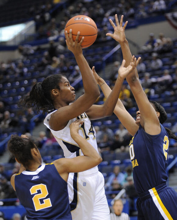 Notre Dame's Devereaux Peters, center, shoots while being guarded by West Virginia's Taylor Palmer, left, and Asya Bussie.