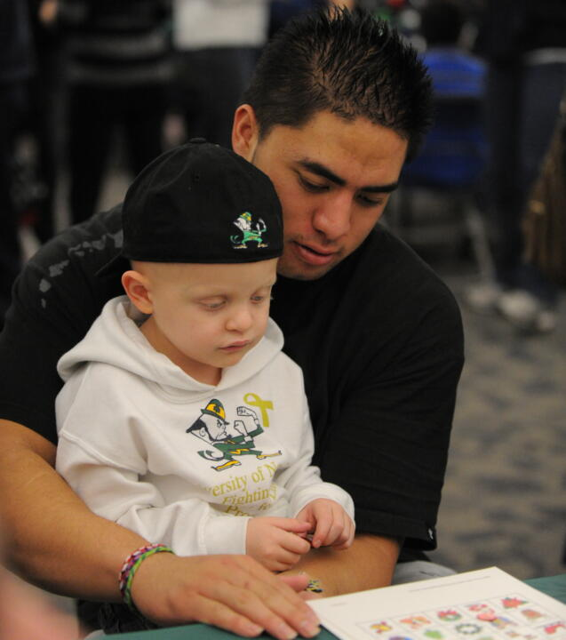 Senior linebacker Manti Te'o helps a young patient read at the Hematology/Oncology Pediatric Christmas Party.