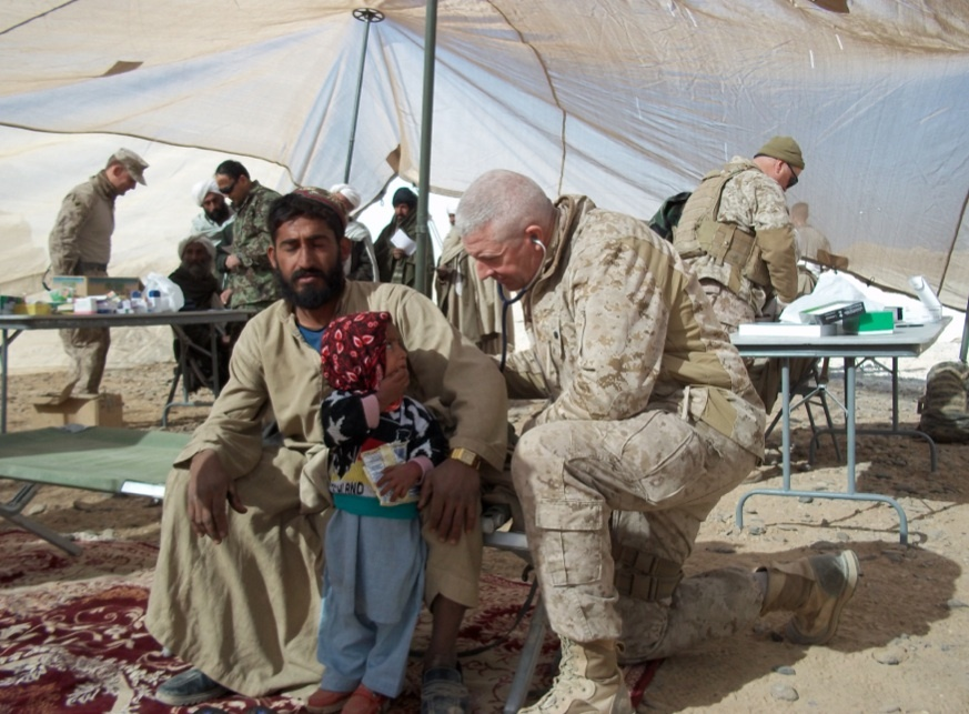 Roy Seitz ('74, fencing) provides medical care for a young Afghan girl. In addition to his work with U.S. Marines, Seitz aided many innocent Afghan villagers who were persecuted by the Taliban.