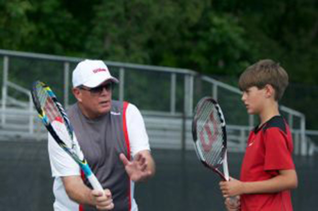Men's Tennis head Coach Bobby Bayliss instructs the next generation of tennis player how to hit a forehand ball.