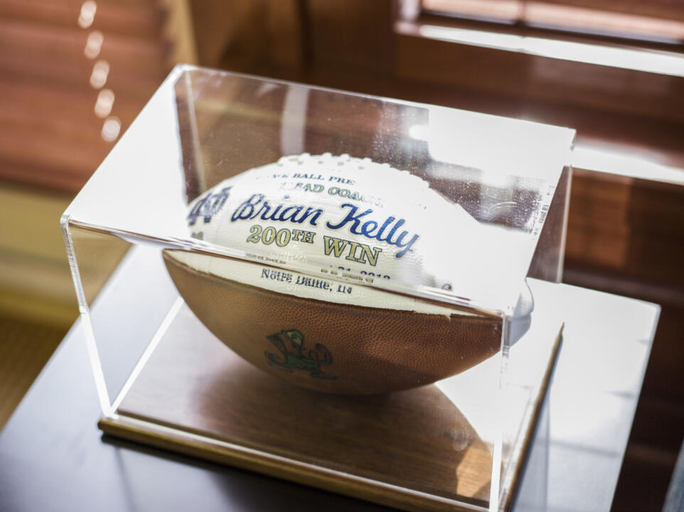 Amongst other footballs featured in his office, Brian Kelly's 200th career win ball is centered in a case.