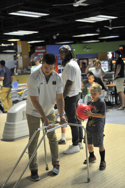 Junior safety Drew Recker helps a child with his bowling game at Strikes 'N' Spares Bowling Alley during an Charity Event Sunday.