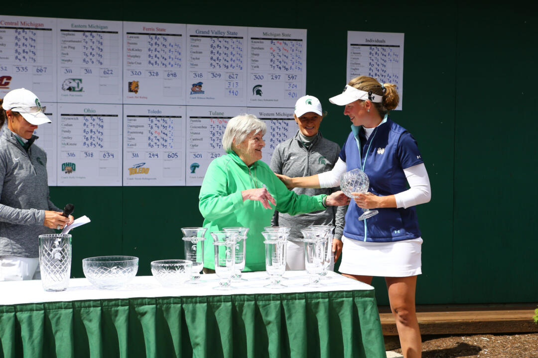Senior captain Talia Campbell accepts the Mary Fossum Invitational individual runner-up trophy from tournament namesake (and former Michigan State coach) Mary Fossum after Campbell's 218 (+2) propelled Notre Dame to a 14-shot win on Sunday in East Lansing, Michigan.