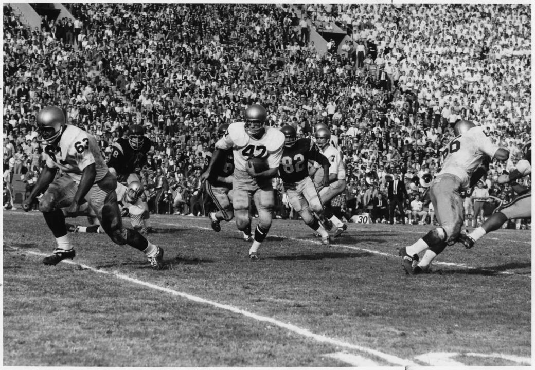 Player Nick Eddy (#47) running with the ball while Dick Arrington (#63) and John Atamian (#66) block.