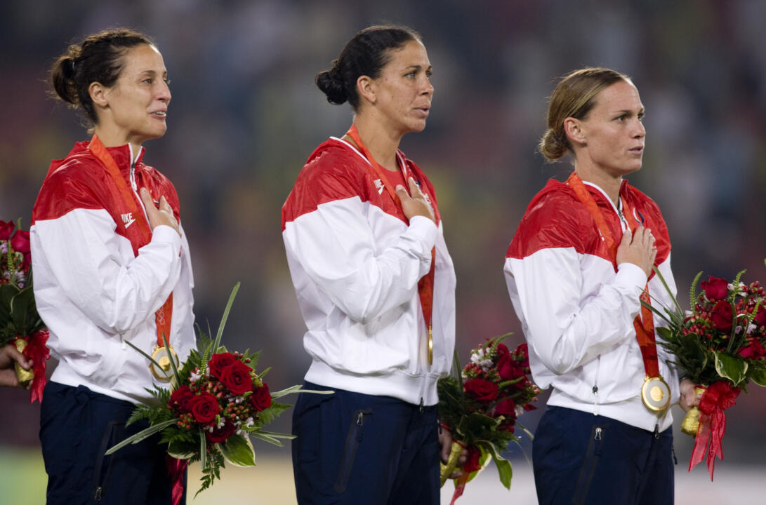 Kate Markgraf, left, is shown with former Irish and USWNT teammate Shannon Boxx and Christie Rampone during the medal ceremony at the 2008 Beijing Olympics, where the U.S. won gold. Markgraf will join the ESPN coverage team as a color commentator for UEFA EURO 2016 to become the first woman to call a major men's soccer tournament on American television.